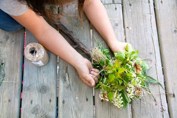 A child ties leaves, flowers and plants around a stick.