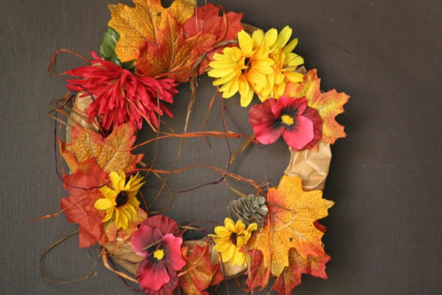 A wreath made from paper bags and plastic flowers.