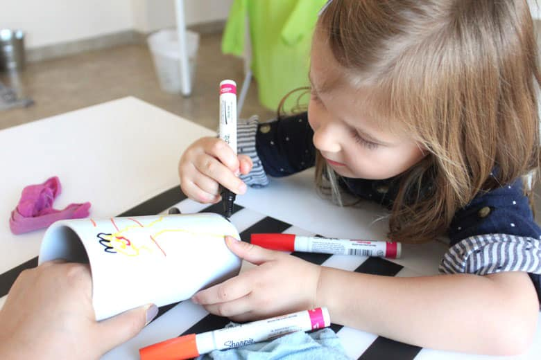 A child drawing on a white mug with porcelain markers.