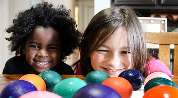 Kids smile into the camera with dyed eggs in the foreground