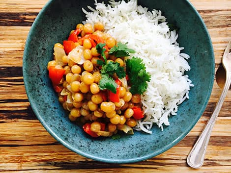 A bowl of chickpea curry served with rice.
