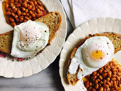 Poached eggs on toast with servings of baked beans.