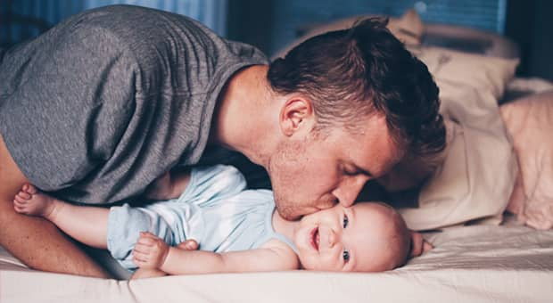 A father gives his baby girl a kiss