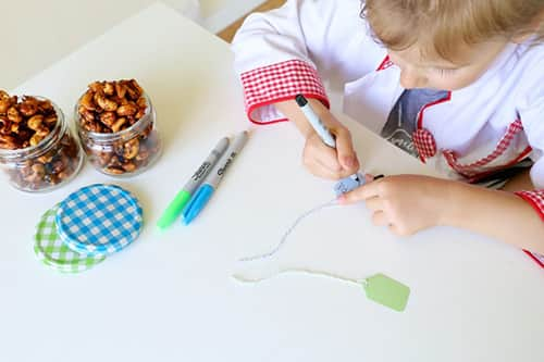 A girl decorates a tag for a jar of nuts.