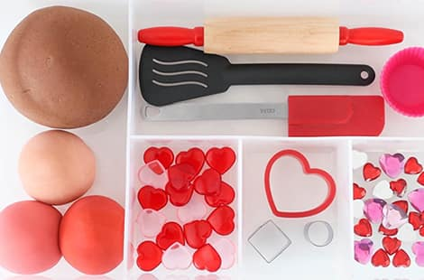 Play dough, kitchen utensils, jewels and cookie cutters in compartments.