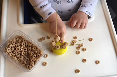 Child adds cereal o's onto dry pasta poking out of playdough.