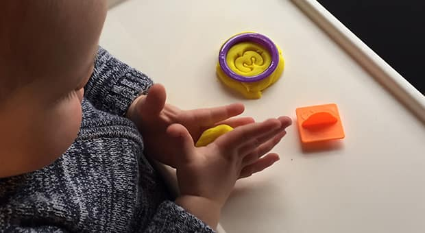 Child plays with play dough in high chair.