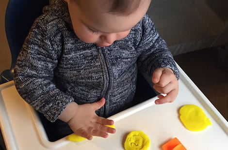 Toddler playing with playdough activity.