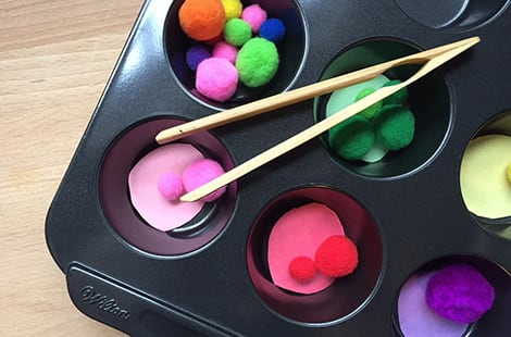 Colourful Pom-poms and construction paper sorted in muffin tin.