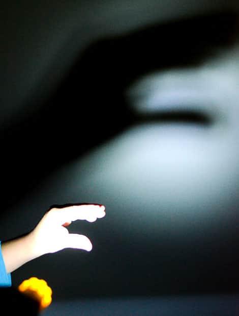 Ребенок с помощью его руку, чтобы сделать тень марионетка на стене.