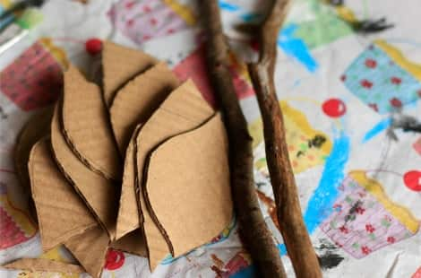 A pile of leaves cut out of cardboard beside two sticks on a tablecloth