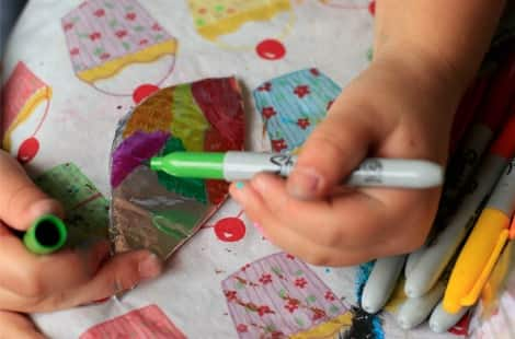 A child uses a green sharpie to colour on the tin foil covered leaf