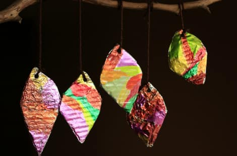 Leaves with hols punched at the top and yarn through them hanging from a stick on a black backdrop
