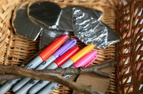 A basket with orange, purple, red, yellow and pink sharpies with a couple sticks and leaf-shaped tin foil