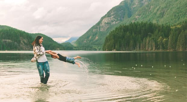A mother and son playing in a lake.