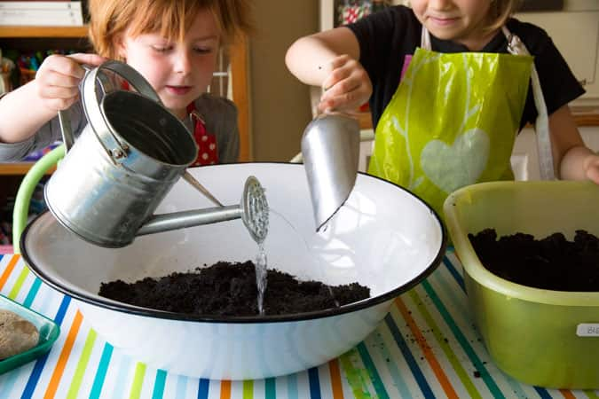 Kids making mud by adding water to a big basin filled with dirt.