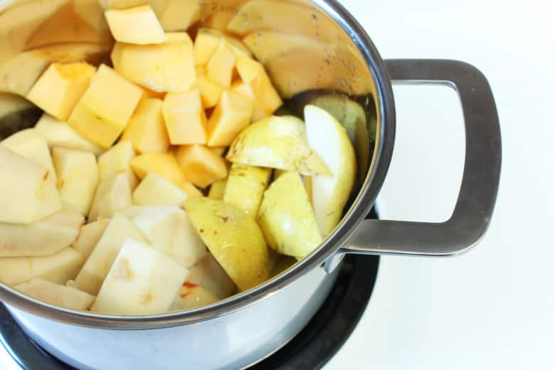 A pot with chopped up fruit and vegetables.