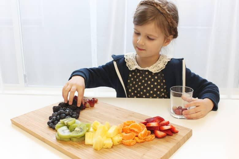 A child arranges fruit in a rainbow shape.