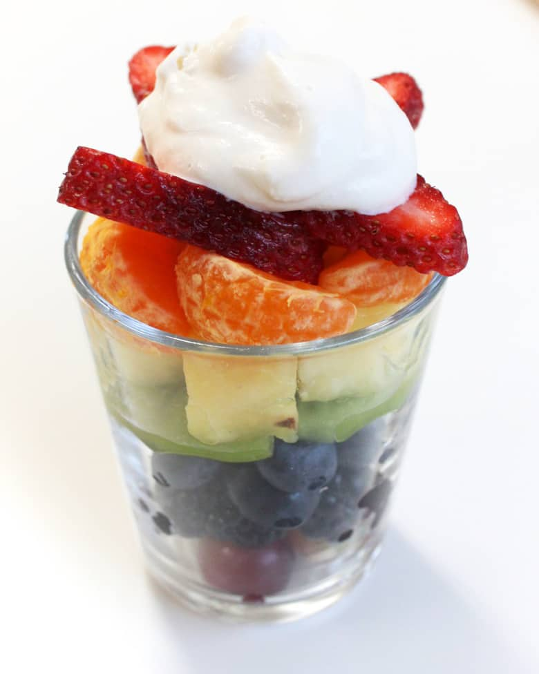 Colourful fruit layered in a small glass, topped with whipped cream.