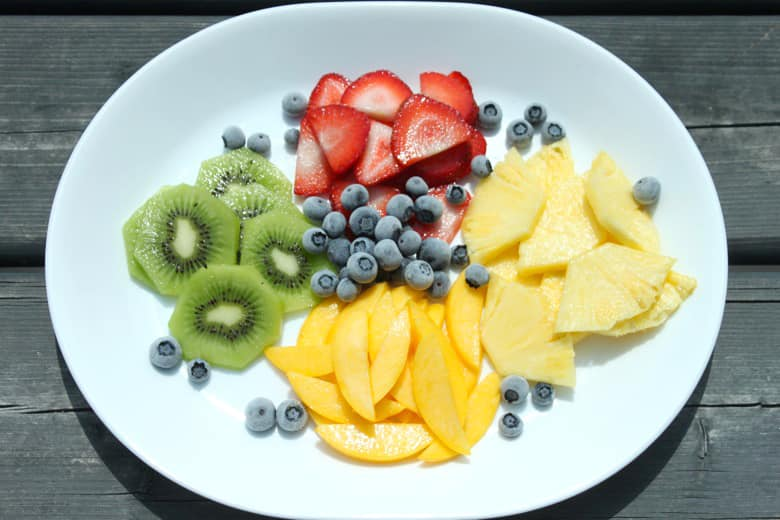 A plate of fresh fruit, including kiwi, strawberry, mango and pineapple.