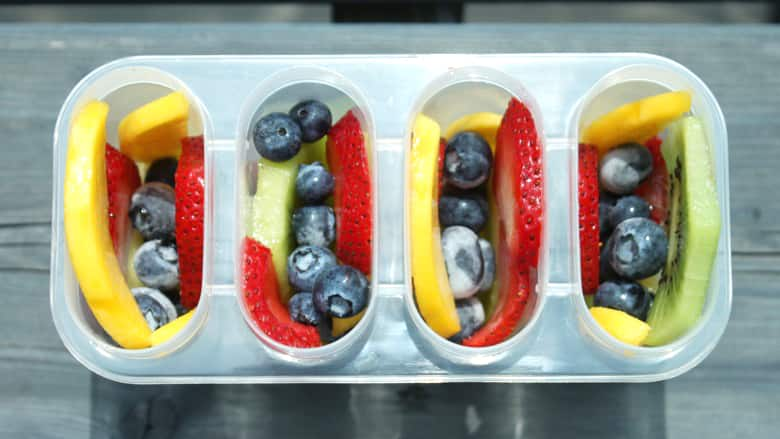 Popsicle moulds filled with fresh fruit.