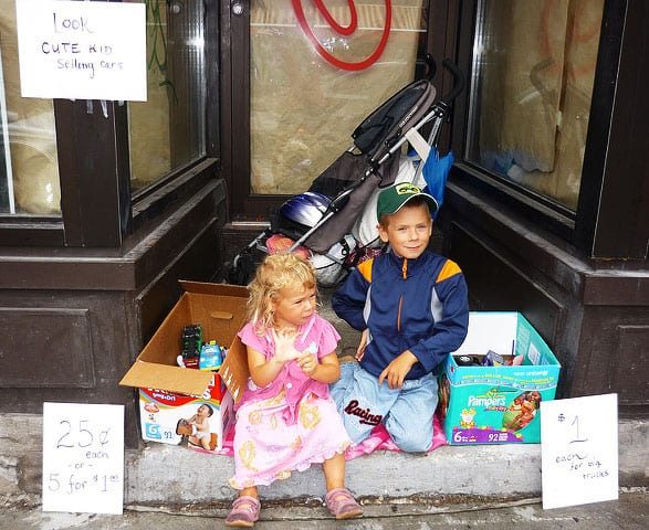 Two kids in a door frame outdoors with boxes of toy cars next to them. One sign says