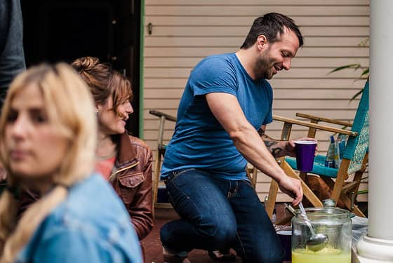 A man at a garage sale, ladeling out a glass of lemonade.