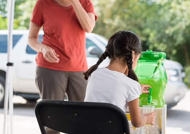 The back of a girl who is sitting at a lemonade stand selling a cup to a customer.