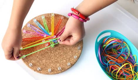 A child making a rainbow flower pattern with colourful elastics.