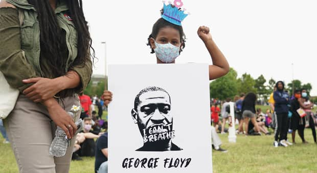 A young girl with a BLM tiara holds up a sign with a picture of George Floyd that says