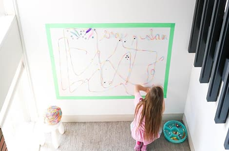 An almost bird's-eye view of child working on wall art.