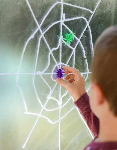 A little boy plays with a purple spider on the web, which already has a green spider stuck to it