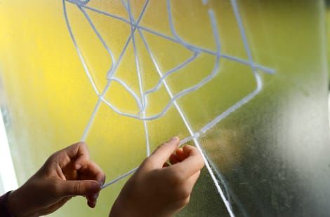 A child's hands placing the white yarn on the contact paper, which is on a window, to create the spider web