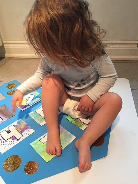 Little girl sits proudly on final project.