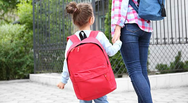 Mother walking daughter to school with noticeably heavy backpack