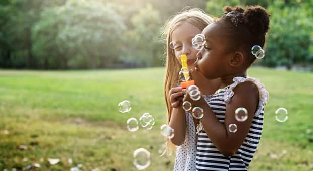 Black and white girl blow bubbles in a field