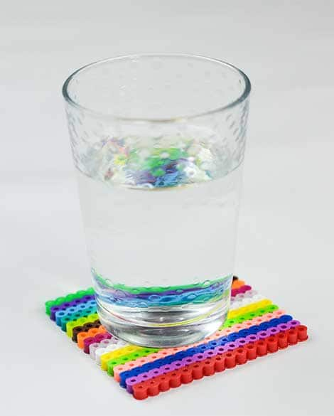 Glass of water on a colourful coaster.