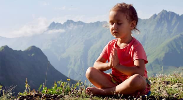 A young child meditates in a beautiful mountain setting.