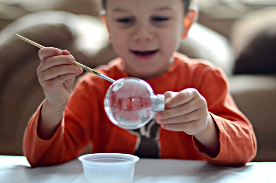 A kid paints on a clear plastic Christmas ornament.