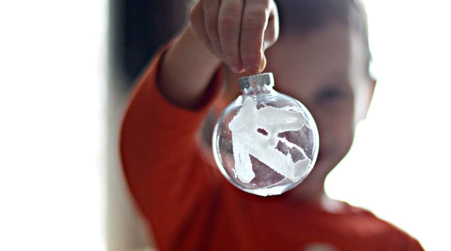 A child holds a clear plastic ornament with the letter K painted on it.