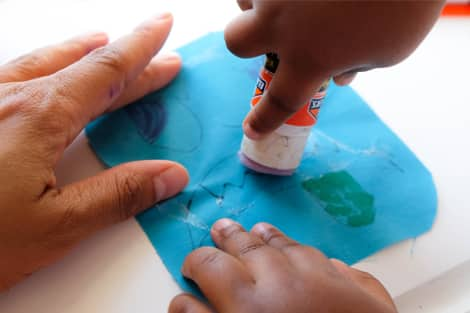 using a glue stick to glue the face on the body