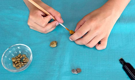 Painting small rocks gold.