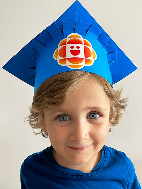 the completed grad cap in blue construction paper, decorated with a CBC Kids gem sticker, being worn by a little boy