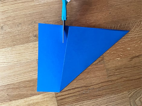 a folded over triangle leaving a strip of paper to cut off