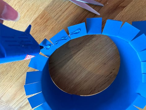 the circular base of the grad cap with tabs folded outward from the centre with glue applied to the tabs