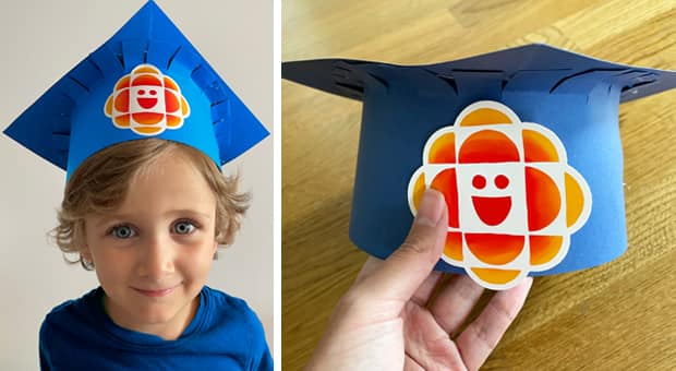 A little boy wearing a DIY mortarboard, or graduation cap, made from blue construction paper with a CBC Kids gem sticker on it