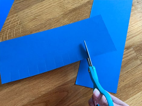 cutting one-inch slits along the side of each rectangle piece