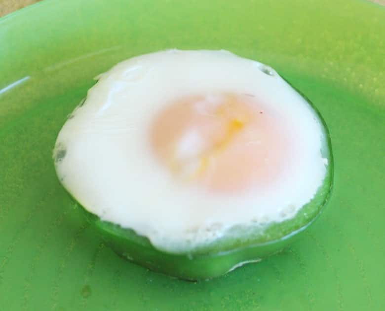 A cooked egg inside of a ring of green pepper.