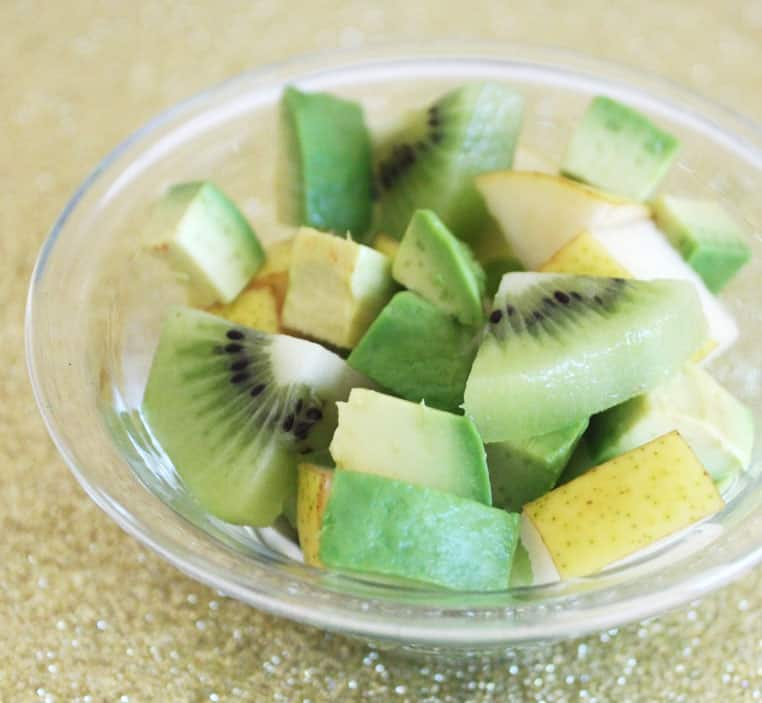 A green fruit salad of kiwi, pear and avocado in a glass bowl.