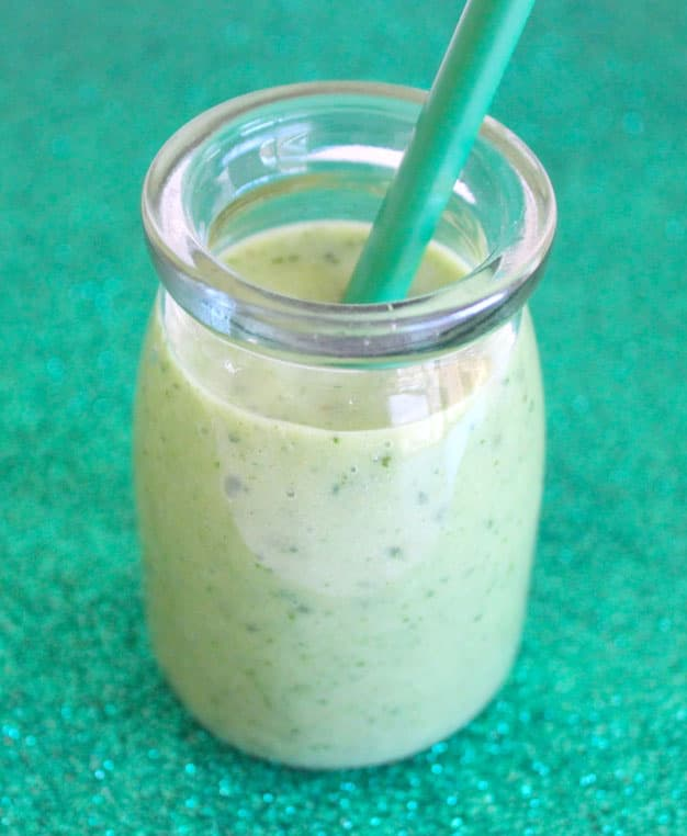 A green smoothie in a small glass with a green straw.